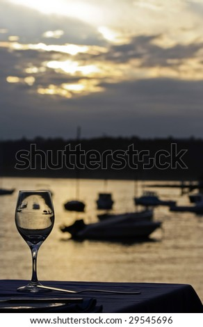 single wine glass at sunset - stock photo