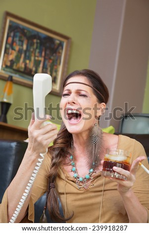Single woman with drink singing into telephone - stock photo