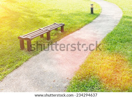 Single Wooden Bench at the Park, with Fresh Green Grasses, Along Narrow Human Pathway. - stock photo