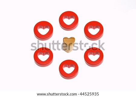 single wooden heart surrounded by six red hearts - stock photo
