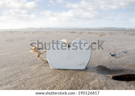 single wooden love heart in the sand on a wild Atlantic way Irish beach in summer - stock photo