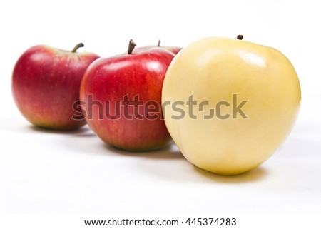 Single yellow apple in front of group of red apple. Group of juicy ripe fruits.  Isolated on white background. - stock photo