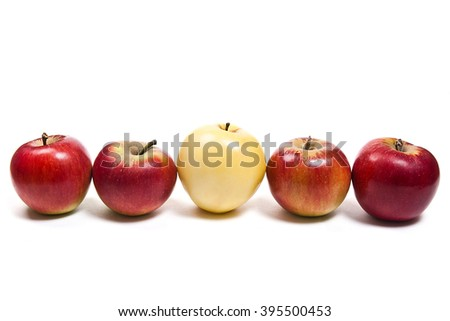 Single yellow apple in middle of group of red apple. Group of juicy ripe fruits.  Isolated on white background. - stock photo
