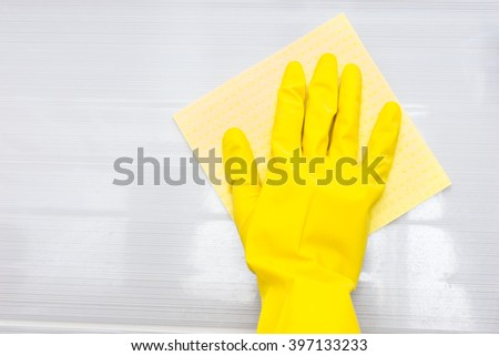 Single yellow rubber gloved hand wiping gray tile surface with square shaped cloth and copy space - stock photo