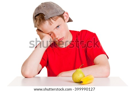 Single young boy in red shirt, backward hat and hand on cheek with bored expression sitting in front of green pear and yellow banana over white background - stock photo