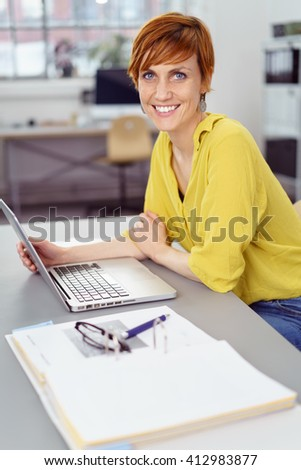 Single young happy red haired woman seated and leaning forward at gray desk with open laptop computer in office - stock photo