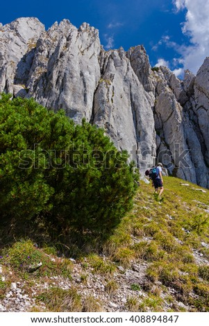 Single young man visiting Piatra Craiului Mountains in the Southern Carpathians in Romania - stock photo