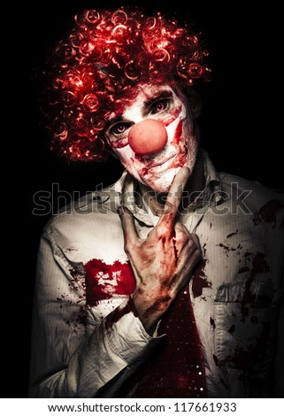 Sinister Bloodstained Clown In A Curly Red Wig Standing Pensively Contemplating His Next Murder Victim With A Dispassionate Look, Halloween Horror Concept - stock photo