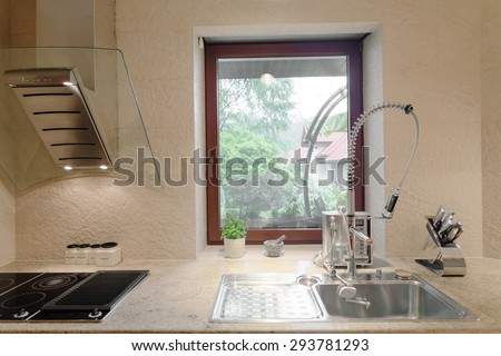 Sink with designed faucet and induction hob - stock photo