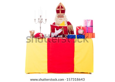 Sinterklaas is working at his desk, at a white background - stock photo