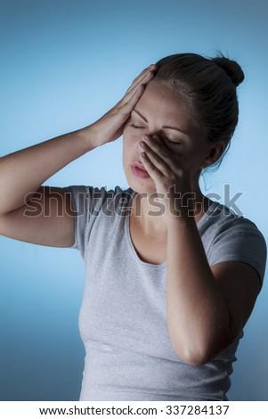 Sinus pain, sinus pressure, sinusitis. Sad woman holding her nose and head because sinus pain - stock photo