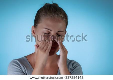 Sinus pain, sinus pressure, sinusitis. Sad woman holding her nose because sinus pain - stock photo