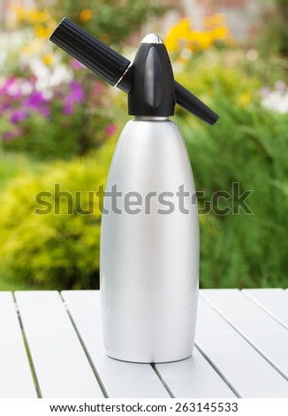 Siphon with soda on garden table - stock photo