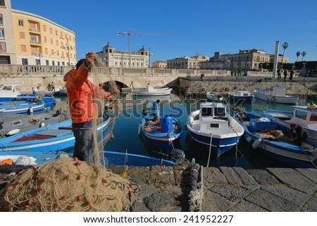 SIRACUSA, ITALY - JAN 03: fishing boats and fisherman in the darsena of Ortigia, Old Town of Siracusa in Sicily. The fisherman in foreground checks and arranges a fishing net. Shot in 2015  - stock photo