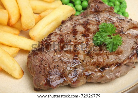 Sirloin beef steak with chips and peas. - stock photo