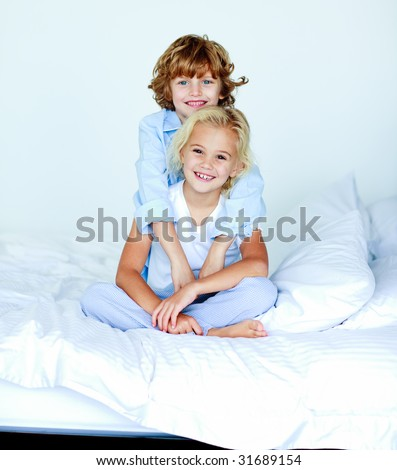 Sister and brother embracing in bed - stock photo