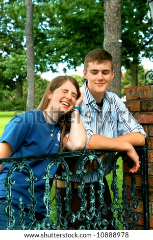 Sister and brother have a good laugh while visiting a park.  Black iron gate.  Sister is laughing hilariously. - stock photo