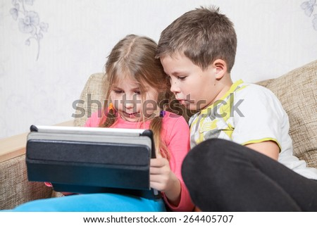 Sister and brother having fun with tablet pc while sitting on sofa together - stock photo