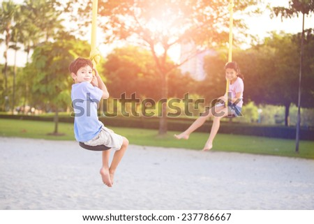Sister and brother in playground swing outdoors - stock photo