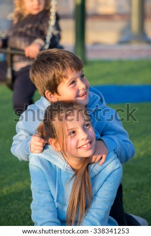 Sister and brother in the same blue jackets play in the playground. Adorable kids - stock photo