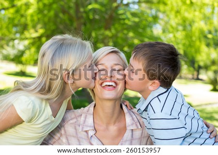 Sister and brother kissing their mother on a sunny day - stock photo