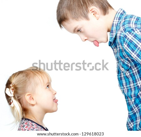 Sister and brother stick out tongues to each other - stock photo