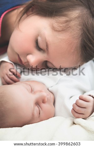 Sister and her newborn brother sleeping - stock photo
