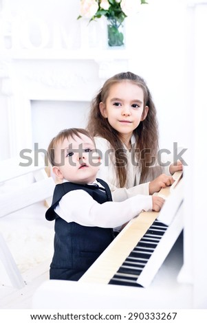 Sister and younger brother Playing Piano together - stock photo