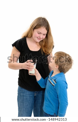 Sister Handing Little Brother his Milk - stock photo