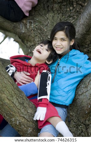 Sister holding disabled brother in tree - stock photo