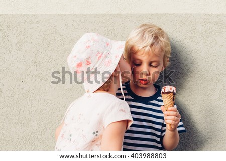 Sister kissed brother who eats ice cream - stock photo