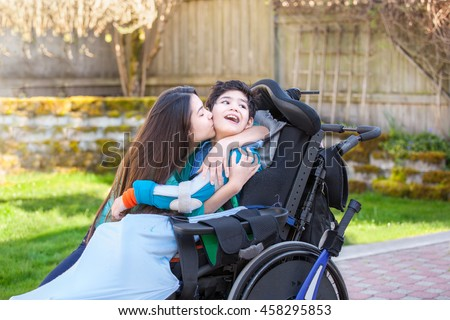 Sister kissing and hugging disabled little nine year old  brother in wheelchair outdoors - stock photo