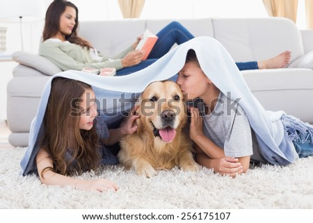 Sister looking at brother kissing dog under shawl while mother relaxing on sofa at home - stock photo