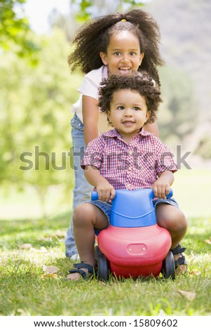 Sister pushing brother on toy with wheels smiling - stock photo