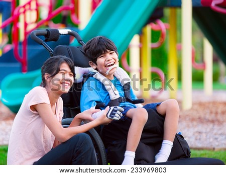 Sister sitting next to disabled brother in wheelchair at playground - stock photo