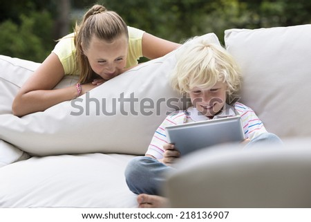 Sister watching brother with digital tablet on outdoor sofa - stock photo