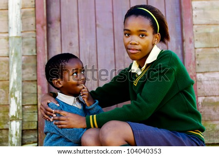 Sister with her little brother on the porch of their home. - stock photo