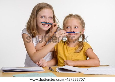 Sisters are playing together in the school. Children crossed their hands and put pencil and brush over mouthes. Funny little girls with awesome smiles. - stock photo