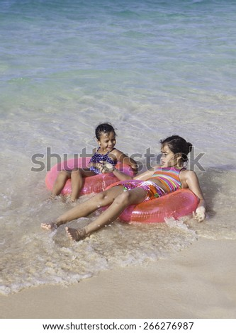 sisters at the beach with float rings - stock photo