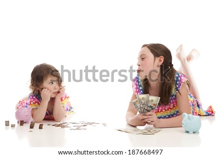 Sisters counting their money.  The older gloating that she has more and the younger pouting.  Isolated on white with room for your text. - stock photo