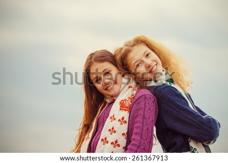Sisters Friendship.Happy smiling two little sisters, girls, schoolgirls over sky background. - stock photo