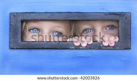 sisters hiding behind a door peeping thru a letter box - stock photo
