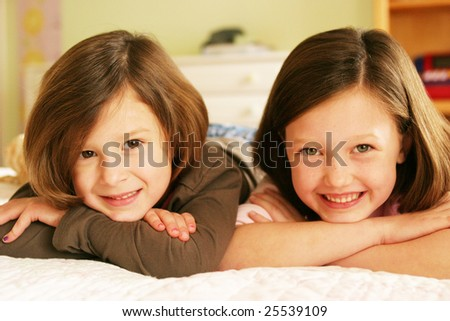 Sisters laying on bed - stock photo