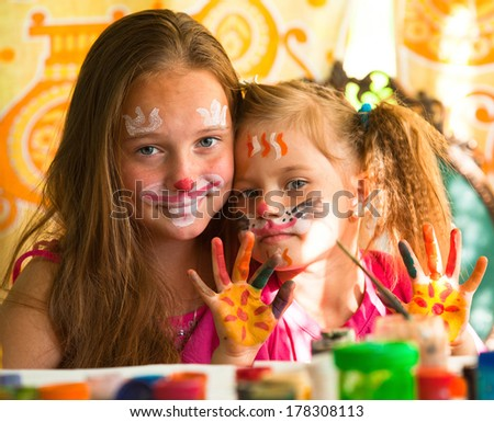 Sisters playing with painting. - stock photo