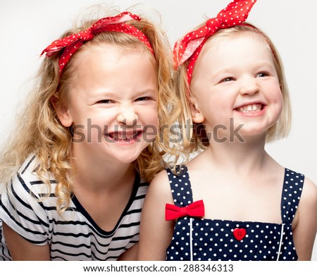 Sisters posing with cheeky grins - stock photo