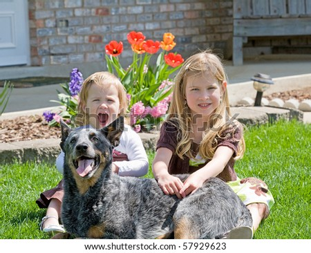 Sisters Sitting With Their Dog in Front of Their House - stock photo