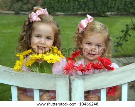 Sisters stand by white, wooden garden gate.  They have picked bouquets for their mom. - stock photo