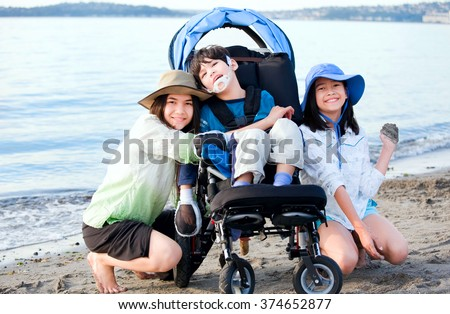 Sisters taking care of disabled brother in wheelchair on beach - stock photo