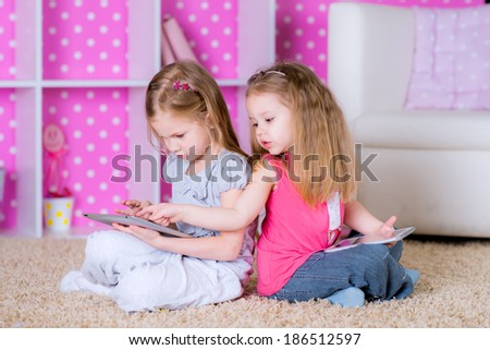 sisters  using modern tablet computers laying on the floor in the polka-dot bright pink room at home fun game  - stock photo