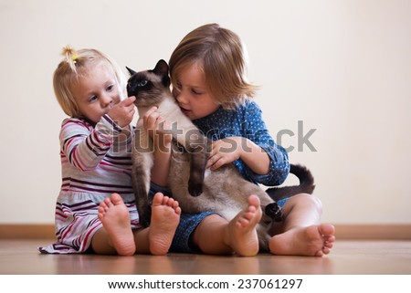 sisters  with cat sitting on the floor   - stock photo